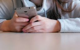 Νέα σοβαρά ανάγνωση γυναικών κάτι στην κινητή τηλεφωνική συνεδρίασή της στον καφέ χέρια κινηματογραφήσεων σε πρώτο πλάνο Στοκ Εικόνες