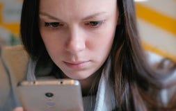 Νέα σοβαρά ανάγνωση γυναικών κάτι στην κινητή τηλεφωνική συνεδρίασή της στον καφέ Πρόσωπο κινηματογραφήσεων σε πρώτο πλάνο Στοκ φωτογραφίες με δικαίωμα ελεύθερης χρήσης