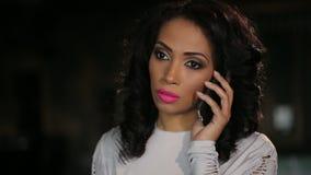 Νέα σοβαρή γυναίκα που μιλά τηλεφωνικώς φιλμ μικρού μήκους