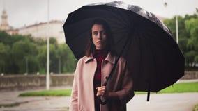 Νέα σοβαρή γυναίκα που στέκεται κάτω από την ομπρέλα στη βροχή, λυπημένος καιρός στην πόλη απόθεμα βίντεο