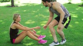 Νέα στάση γυναικών βοήθειας ανδρών αθλητών επάνω από τον πράσινο χορτοτάπητα Ομαδική εργασία αθλητικών ανθρώπων φιλμ μικρού μήκους