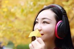 Νέα στάση γυναικών κάτω από τη θάλασσα δέντρων και άκουσμα τη μουσική με τα ακουστικά στοκ φωτογραφία με δικαίωμα ελεύθερης χρήσης