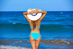 Νέα στάση κοριτσιών που εξετάζει το καπέλο παραλιών θάλασσας στοκ εικόνα