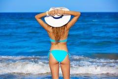 Νέα στάση κοριτσιών που εξετάζει το καπέλο παραλιών θάλασσας στοκ φωτογραφία με δικαίωμα ελεύθερης χρήσης