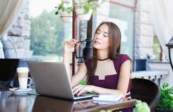 Νέα στοχαστική επιχειρηματίας που εργάζεται στο lap-top και που κάνει τις σημειώσεις Στοκ εικόνες με δικαίωμα ελεύθερης χρήσης
