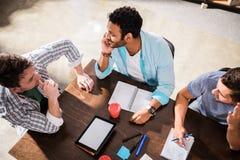 Νέα συγκεντρωμένα άτομα που εργάζονται στο πρόγραμμα στη μικρή συνεδρίαση των γραφείων Στοκ Φωτογραφία