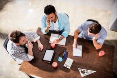 Νέα συγκεντρωμένα άτομα που εργάζονται στο πρόγραμμα στη μικρή συνεδρίαση των γραφείων Στοκ Εικόνα
