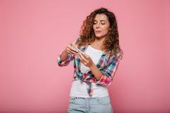 Νέα συγκεντρωμένα γυναικεία παίζοντας παιχνίδια στο smartphone που απομονώνονται Στοκ Φωτογραφίες