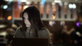 Νέα συγκεντρωμένη γυναίκα που εργάζεται στον καφέ το βράδυ Θηλυκό Brunette χρησιμοποιώντας το lap-top και μιλώντας στο τηλέφωνο φιλμ μικρού μήκους