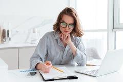 Νέα συγκεντρωμένη επιχειρηματίας στα γυαλιά και το ριγωτό πουκάμισο wo στοκ φωτογραφία