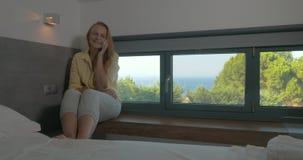 Νέα συγκινημένη γυναίκα που μιλά σε κινητό στο ξενοδοχείο φιλμ μικρού μήκους