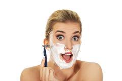Νέα συγκλονισμένη γυναίκα που ξυρίζει το πρόσωπό της με ένα ξυράφι στοκ εικόνες