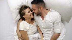 Νέα συζήτηση και αγκάλιασμα όμορφων και ζευγών αγάπης στο κρεβάτι ξυπνώντας το πρωί Τοπ άποψη του ελκυστικού ατόμου φιλμ μικρού μήκους