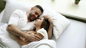 Νέα συζήτηση και αγκάλιασμα όμορφων και ζευγών αγάπης στο κρεβάτι ξυπνώντας το πρωί Τοπ άποψη του ελκυστικού ατόμου απόθεμα βίντεο