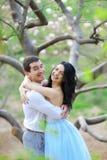 Νέα συμπαθητικά θηλυκά πρόσωπο και άτομο brunette που αγκαλιάζουν κοντά στο ανθίζοντας δέντρο στοκ εικόνα
