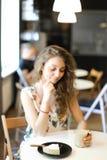 Νέα συμπαθητική συνεδρίαση γυναικών με το κέικ και το φλιτζάνι του καφέ στον καφέ στοκ εικόνες