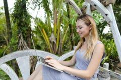 Νέα συμπαθητική συνεδρίαση κοριτσιών στην ταλάντευση και χρησιμοποίηση του lap-top, φοίνικες στο υπόβαθρο στοκ εικόνες με δικαίωμα ελεύθερης χρήσης