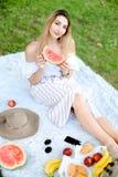 Νέα συμπαθητική συνεδρίαση κοριτσιών στο καρό κοντά στα φρούτα και το καπέλο, που τρώνε το καρπούζι, χλόη στο υπόβαθρο στοκ εικόνες
