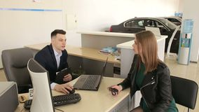 Νέα συνεδρίαση γυναικών και πωλητών στον πίνακα στο σαλόνι αυτοκινήτων Αγοράζοντας αυτοκίνητο απόθεμα βίντεο