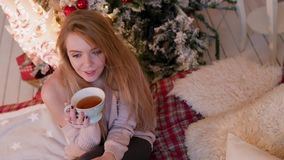 Νέα συνεδρίαση γυναικών με την κούπα τσαγιού στο εσωτερικό Χριστουγέννων Απολαύστε τις διακοπές απόθεμα βίντεο