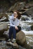 Νέα συνεδρίαση γυναικών σε έναν βράχο στη μέση ενός ποταμού κρατώντας το πηγούνι της με ένα χέρι στοκ φωτογραφία