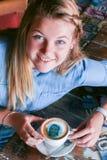 Νέα συνεδρίαση γυναικών σε έναν πίνακα που κρατά ένα φλυτζάνι καφέ με το πρόσωπό της που τυπώνεται στον αφρό Στοκ εικόνα με δικαίωμα ελεύθερης χρήσης