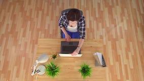 Νέα συνεδρίαση γυναικών σε ένα ορθοπεδικό πράσινο μαξιλάρι από τα hemorrhoids που λειτουργεί σε ένα lap-top, τοπ άποψη απόθεμα βίντεο