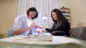 Νέα συνεδρίαση γυναικών σε μια καρέκλα σε ένα σαλόνι καρφιών, μανικιουρίστας που κάνει τον πελάτη μανικιούρ απόθεμα βίντεο