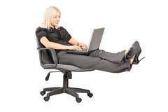 Νέα συνεδρίαση γυναικών στην έδρα γραφείων με τα πόδια της επάνω και εργαζόμενος Στοκ Φωτογραφίες