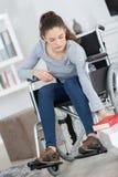Νέα συνεδρίαση γυναικών στην αναπηρική καρέκλα που φθάνει στο βιβλίο Στοκ Φωτογραφίες