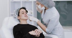 Νέα συνεδρίαση γυναικών στην καρέκλα επισκεμμένος μια όμορφη θηλυκή προετοιμασία cosmetologist για τις καλλυντικές διαδικασίες απόθεμα βίντεο