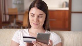 Νέα συνεδρίαση γυναικών στον καναπέ στην αγορά καθιστικών on-line με την πιστωτική κάρτα στο smartphone απόθεμα βίντεο