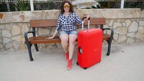 Νέα συνεδρίαση γυναικών στον πάγκο με τη βαλίτσα απόθεμα βίντεο