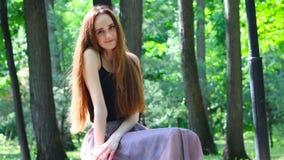 Νέα συνεδρίαση γυναικών στον πάγκο στο πάρκο απόθεμα βίντεο