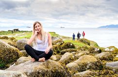 Νέα συνεδρίαση γυναικών στο βράχο και χαμόγελο φιλικό στη κάμερα Στοκ φωτογραφία με δικαίωμα ελεύθερης χρήσης