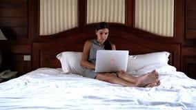 Νέα συνεδρίαση γυναικών στο κρεβάτι και εργασία σε ένα lap-top 4K φιλμ μικρού μήκους