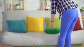 Νέα συνεδρίαση γυναικών στο ορθοπεδικό στρογγυλό μαξιλάρι στον καναπέ απόθεμα βίντεο
