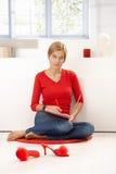 Νέα συνεδρίαση γυναικών στο πάτωμα στο κόκκινο γράψιμο Στοκ Εικόνα