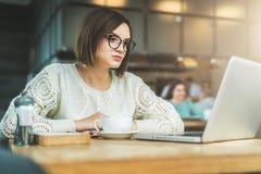 Νέα συνεδρίαση επιχειρηματιών στον καφέ στον πίνακα και εργασία στο lap-top Στο επιτραπέζιο φλιτζάνι του καφέ Σπουδαστής που μελε Στοκ εικόνες με δικαίωμα ελεύθερης χρήσης