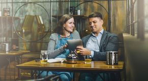 Νέα συνεδρίαση ζευγών αγάπης στον καφέ στον πίνακα και χρησιμοποίηση του υπολογιστή ταμπλετών Ψηφιακή συσκευή χρήσης κοριτσιών κα Στοκ φωτογραφίες με δικαίωμα ελεύθερης χρήσης