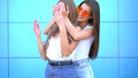 Νέα συνεδρίαση των γυναικών hipster δύο και αγκάλιασμα πέρα από τον μπλε τοίχο απόθεμα βίντεο