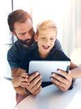 Νέα συνεδρίαση αγοριών με τον πατέρα στον πίνακα και τη χρησιμοποίηση της ταμπλέτας PC στη σύγχρονη σοφίτα Κάθετο, θολωμένο υπόβα Στοκ Φωτογραφίες