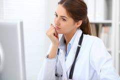 Νέα συνεδρίαση γιατρών brunette θηλυκή στον πίνακα και εργασία στο γραφείο νοσοκομείων στοκ φωτογραφία με δικαίωμα ελεύθερης χρήσης