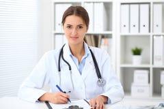 Νέα συνεδρίαση γιατρών brunette θηλυκή στον πίνακα και εργασία στο γραφείο νοσοκομείων Στοκ Εικόνες
