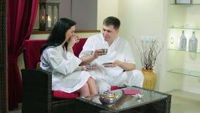 Νέα συνεδρίαση γυναικών και ανδρών στο τσάι κατανάλωσης καναπέδων απόθεμα βίντεο