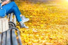 Νέα συνεδρίαση γυναικών σε έναν πάγκο στο πάρκο Στοκ Εικόνες