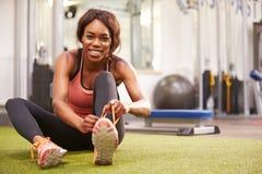Νέα συνεδρίαση γυναικών σε μια γυμναστική που δένει τα κορδόνια της Στοκ Φωτογραφία