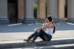 Νέα συνεδρίαση γυναικών στα σκαλοπάτια και άκουσμα τη μουσική Στοκ φωτογραφία με δικαίωμα ελεύθερης χρήσης
