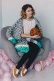 Νέα συνεδρίαση γυναικών στην καρέκλα με την πορτοκαλιά μερινός σφαίρα μαλλιού Στοκ Φωτογραφίες