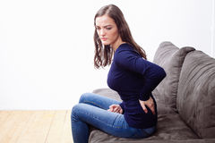 Νέα συνεδρίαση γυναικών στον καναπέ που πάσχει από τον πόνο Στοκ φωτογραφία με δικαίωμα ελεύθερης χρήσης